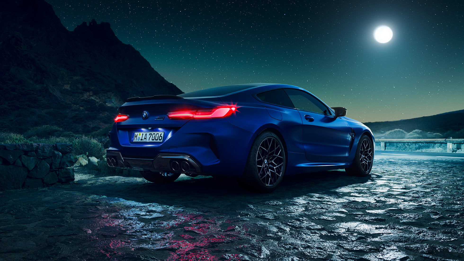BMW M8 Competition Coupé in Marina Bay Blue metallic with illuminated LED rear lights, standing three-quarter rear view with full moon.