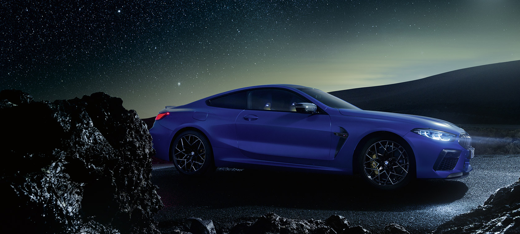 BMW M8 Competition Coupé,, side view, driving at night with full moon.