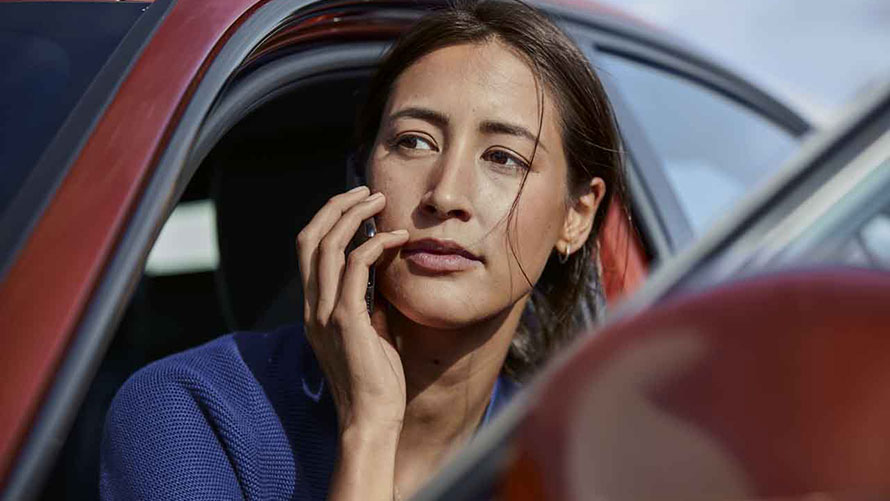 Woman on her phone looking out from her BMW